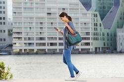 Full body side portrait of young woman walking by the water using cell phone