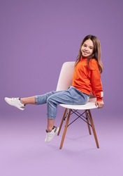 Full body side view of smiling little girl in orange sweatshirt and jeans with white sneakers sitting on chair in studio against violet background