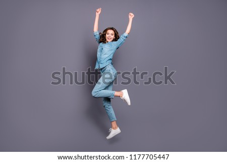 Full body size length of nice crazy cheerful attractive brunette girl with wavy hair in casual denim shirt and jeans, jumping in air, dancing, celebrating, isolated over grey background