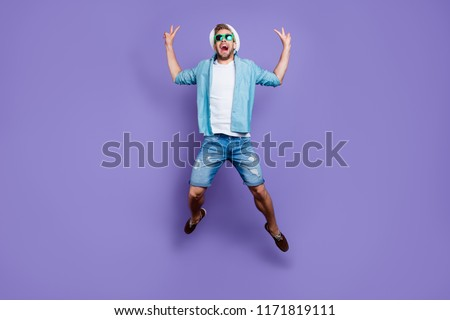 Full body size length photo of attractive trendy handsome guy wearing casual, color sun glasses and sunhat, jumping in air on holiday, double v-sign, freedom over bright violet purple background