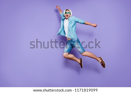 Full body size length photo of trendy handsome guy on vacation wearing casual blue jeans, color sun glasses and sunhat, rushing far away in air to rescue, fooling, over pastel violet purple background