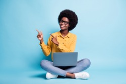 Full body size photo of black skin big volume hairstyle woman sit floor crossed legs hold netbook direct fingers empty space wear specs jeans yellow shirt isolated blue color background