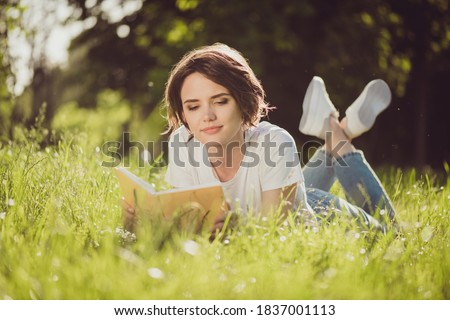 Full body size photo of charming lovely cute lady smiling reading nice romantic novel textbook lying grass in harmony world nature resting wear jeans sneakers white shirt outside Сток-фото ©