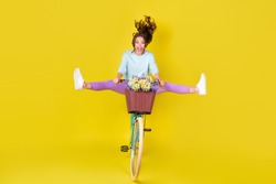 Full body size photo of insane young woman riding vintage unusual bike flying from hill carry flowers wind blow hair wear blue pullover violet pants isolated vibrant yellow color background