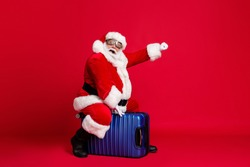 Full body size photo of retired grandpa white beard ride suitcase pretend raise fist playing witch fly broom wear santa x-mas costume spectacles headwear isolated red color background