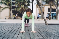 Full body slim middle aged female athlete doing four limbed staff pose of yoga on wooden quay near contemporary building