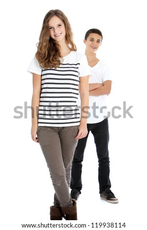 Full body studio portrait of two smiling young trendy teenagers in smart casual clothes with the girl in the foreground and boy behind isolated on white