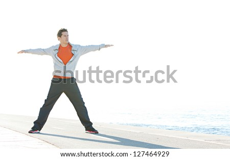 Full body view of a sports man stretching his arms and legs in a star shape while standing on a racing track by the blue sea, with a sunny sky in the background.
