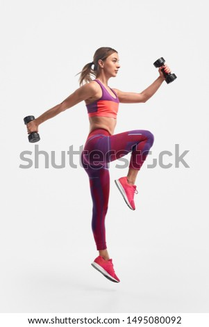 Full body view of muscular young female in sportswear swinging arms with heavy dumbbells and leaping against white background during training for biceps and legs