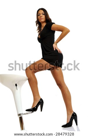 Full body view of sexy brunette with short black dress, posing with a stool. Isolated on white background.