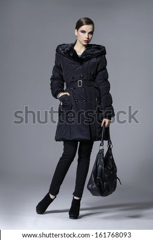 Full body young elegant woman in coat with holding bag posing