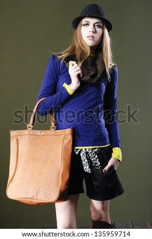 full body young fashion model in hat with bag posing o