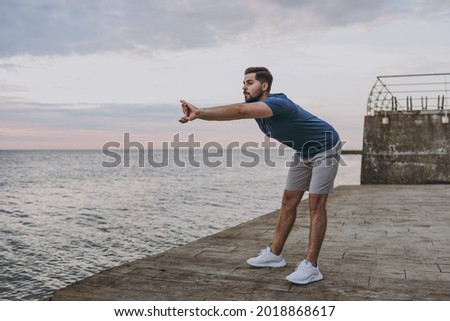 Full body young strong sporty athletic toned fit sportsman man in sports clothes warm up training do stretch hands exercise at sunrise sun over sea beach outdoor on pier seaside in summer day morning. Stok fotoğraf ©