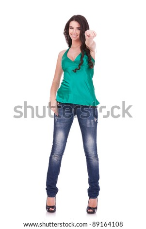 Full body young woman in casual clothes, pointing at you, isolated over a white background.