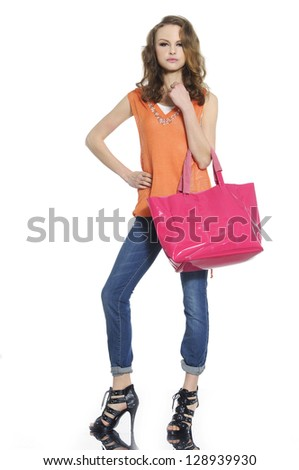 Full body young woman in jeans with red bag posing
