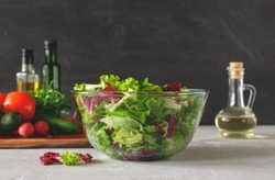 Full bowl of fresh green salad close up on a light table against a dark background on a rustic kitchen. Concept helpful and simple food