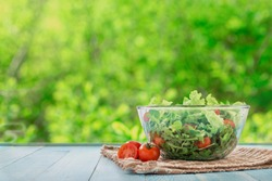 Full bowl of fresh salad on a wooden table  against the background blur green leaves bokeh
