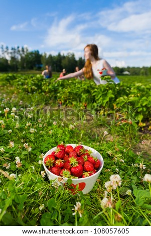 Full bowl of strawberries. Focus on bowl and group of girls behind, vertical format