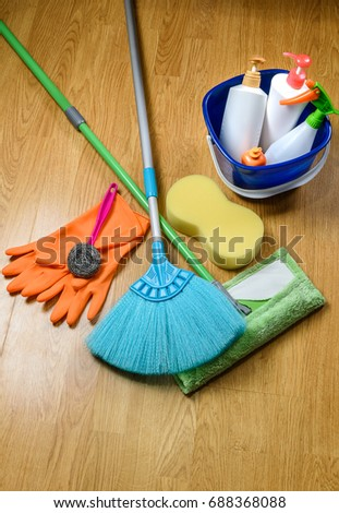 full box of cleaning supplies, mop, broom and gloves on wooden floor background #688368088