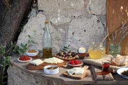 full breakfast brunch table with cheese eggs olives honey bread