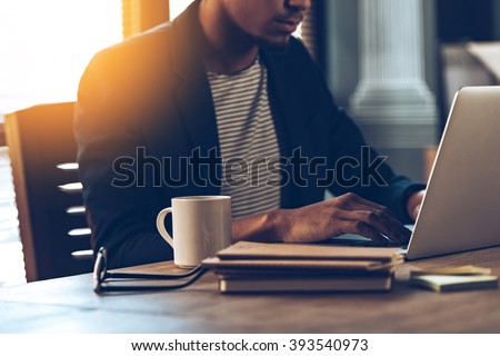 Full concentration. Close-up part of young African man using laptop while sitting at his working place