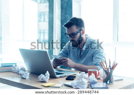 Full concentration on work. Concentrated young beard man looking at his mobile phone while sitting at his working place in office