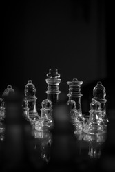 Full contrast scene of a cristal chess game subtly lit over a black background