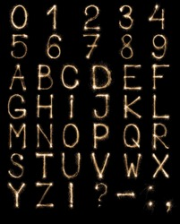 Full english alphabet and numbers set made from burning sparkles on black background. Shiny festive firework latin font.