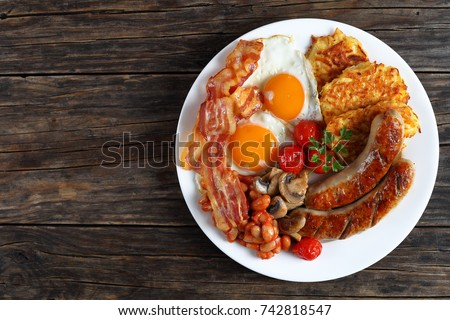 full english breakfast - bean, hash brown, fried eggs sunny side up, bacon slices, sausages, tomatoes, mushrooms on white plate on dark wooden table, view from above  #742818547