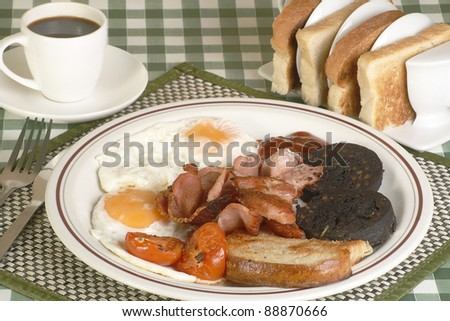 full english breakfast of bacon egg tomato black pudding and fried bread on a gingham cloth