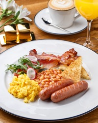 Full English breakfast - scrambled egg, sausages, beans in tomato sauce, brioche, grilled bacon, fresh salad over wooden table with cup of coffee, orange juice and flowers