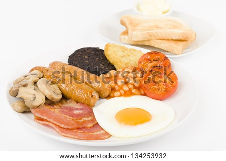 Full English Breakfast - Traditional English fry-up with egg, bacon, mushrooms, tomatoes, sausages, black pudding, hash browns and baked beans. Served with slices of toast and butter.