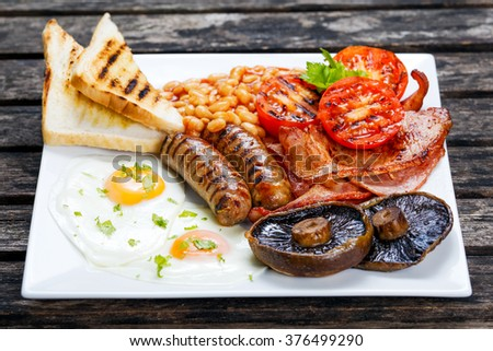 Full English breakfast with bacon, sausage, egg, beans and mushrooms Stock photo ©