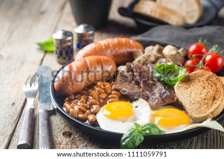 Full English breakfast with fried eggs, sausages, bacon, beans, toast and tomatoes on rustic wooden background Stock photo ©