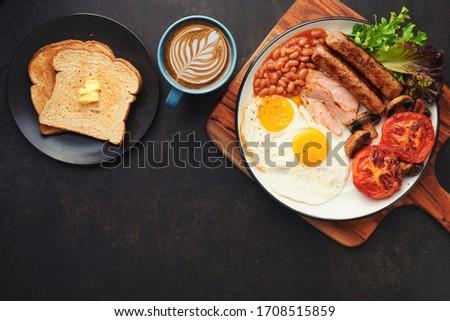 Full English Breakfast with Latte Art on dark table sausage eggs bean bacon tomatos mushroom Stock photo ©