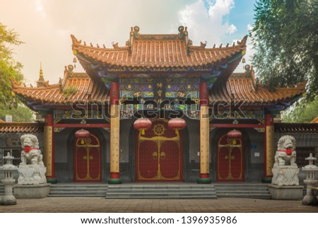 Full entrance of a Lama Temple with couple of Lion Fudogs, lanterns and red lanterns during a cloudy sunset in Harbin