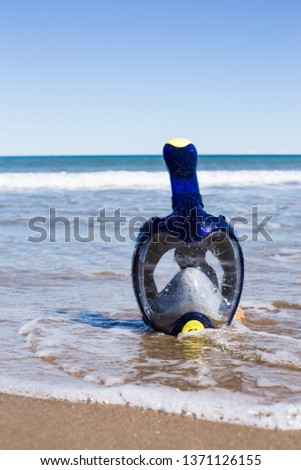 Blue swimming mask on sea beach  face mask on the beach