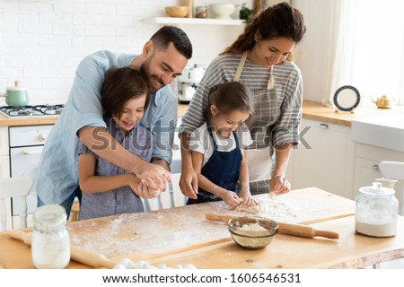 Full family feels happy cooking together gathered in domestic kitchen preparing family recipe pie or dessert, playful siblings helping to parents, mom and dad teaching kids, hobby and pastime concept