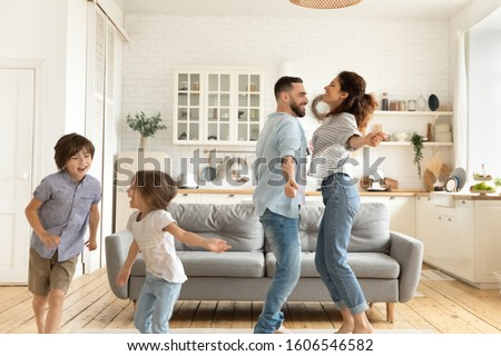 Full family with little children standing in living room feels happy dancing enjoy holidays, celebrating relocation at new modern studio apartments, funny activities with kids, active weekend concept Stockfoto ©