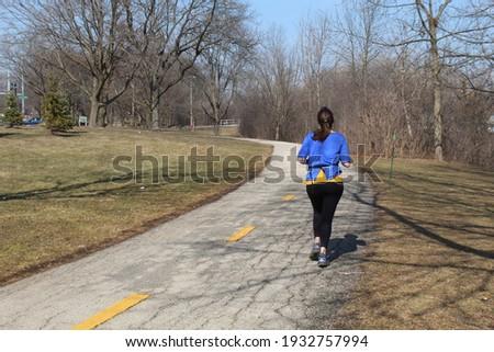 Full-figured woman running a trail at the Skokie Northshore Sculpture Park in Skokie, Illinois Zdjęcia stock ©
