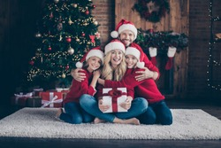 Full four members family dad mom sister brother giving surprise giftbox spending x-mas eve sitting floor near newyear tree indoors wear santa caps and red sweaters