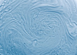 Full frame background liquid texture. Waves and swirls of gel like substance. Blue tone with tiny bubbles.
