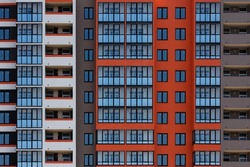 full frame background of freshly build new high rise apartament building wall with multiple balcony and windows