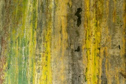 Full frame background of old peeling yellow, green and black wall