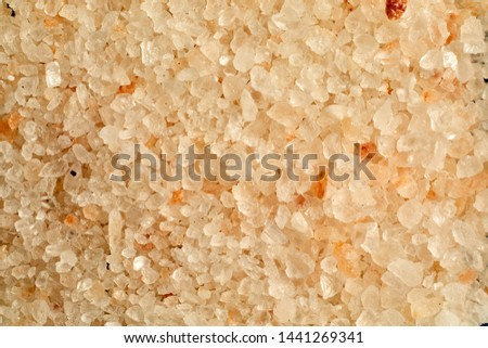 Full frame close up background texture of coarse granules of red Indus hill salt from Punjab Pakistan colored naturally by iron oxides from the area