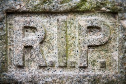 Full frame close-up of RIP Rest In Peace message carved into weathered granite gravestone