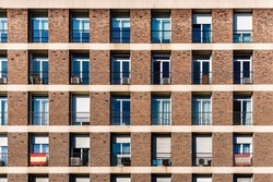 Full frame of brick facade of residential building with array of rectangular windows, some of them with Spanish flag
