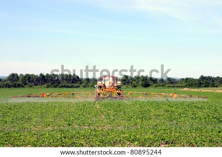 Full frame rear view of tractor spraying pesticides on soy bean crop