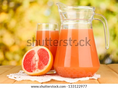 Full glass and jug of grapefruit juice and grapefruits on wooden table outdoor