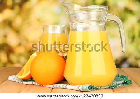 Full glass and jug of orange juice and oranges on wooden table outdoor